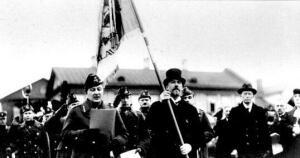 Riigivanem J. Tõnisson hoiab Narva linna poolt 4. jalaväe- rügemendile annetatud lippu enne üleandmist väeosale. N. Reek loeb lipu üleandmise diplomit